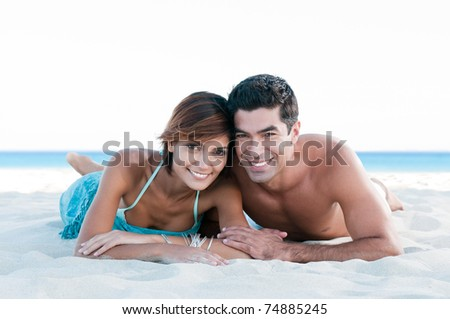 Happy smiling couple relaxing together and lying on sand at summer beach
