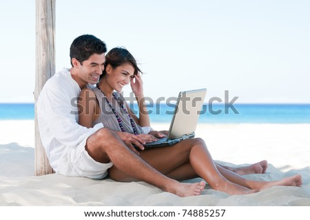 Happy smiling couple surfing the net and enjoy the summer at tropical beach