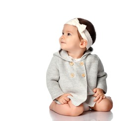 Happy smiling curious child in knitted clothes, headband isolated portrait. Excited infant child looking up over white studio background. Innocence, curiosity, childhood concept. Children's style