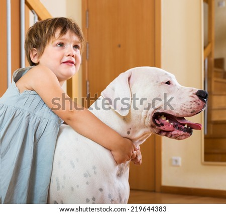 Happy smiling cute little girl hugging big white dog at home