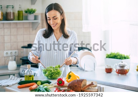 Happy smiling cute woman is preparing a fresh healthy vegan salad with many vegetables in the kitchen at home and trying a new recipe