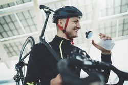 Happy smiling cyclist man drinking water while resting after intensive driving a bike, cheerful young male cyclist holding road bike on shoulder, after sunny morning workout, healthy, sport lifestyle