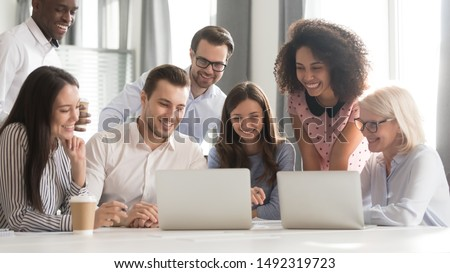 Happy smiling diverse employees using laptop, watching webinar together, engaged in online conference, students, office workers working on project, teamwork concept, horizontal photo