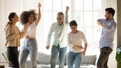 Happy smiling diverse friends dancing to favorite music at home party, having fun on weekend, laughing and singing, funny activity, celebrating indoors, spending free time together