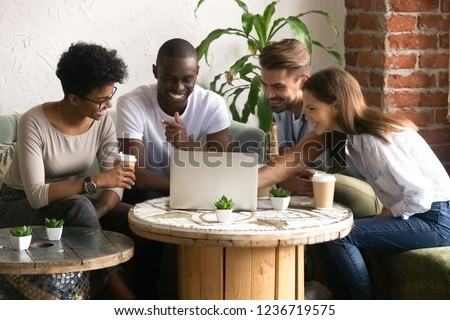 Happy smiling diverse friends using laptop together in cafe, watching funny video online, comedy movie during lunch in coffee house, multiracial people having fun together, free time activities