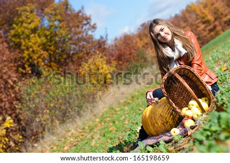 Happy smiling elegant young woman happy smiling & looking at camera with basket of fresh apples sitting on meadow on bright autumn day outdoors background