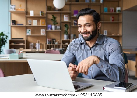 Happy smiling ethnical indian businessman having online virtual meeting call on laptop looking at screen sitting at table in coworking creative office, professional manager talking to employees.