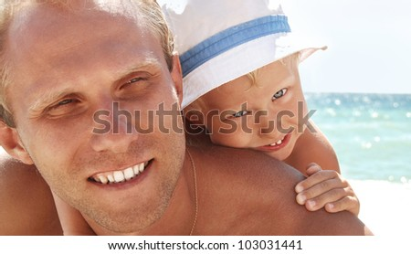 Happy smiling faces father and son at the sea view