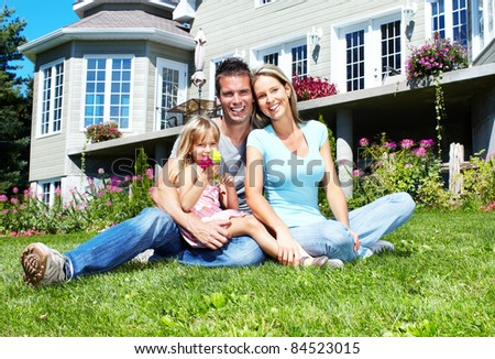 Happy smiling family near new house. Realty.