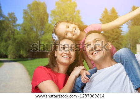 Happy smiling family with daughter over green trees background #1287089614