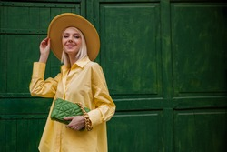 Happy smiling fashionable woman wearing total yellow outfit: wide brim hat, classic shirt,  holding quilted faux leather bag with chain, posing on green background. Copy, empty space for text