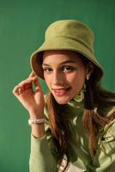 Happy smiling fashionable woman with green eyes makeup, wearing trendy green bucket hat, turtleneck sweater. Total color look, outfit