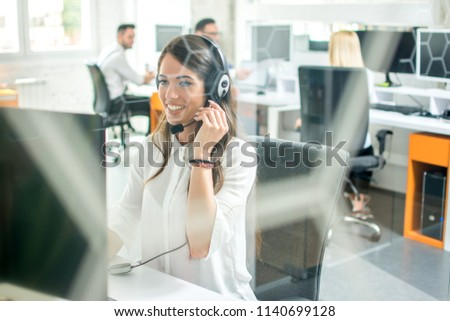 Happy smiling female customer support phone operator at workplace