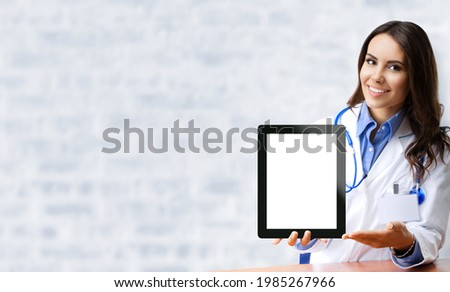 Happy smiling female doctor showing tablet pc iPad touchpad with blank copy space area for slogan or text, over office white brick loft wall. Medical call center concept. Zoom, Skype video conference. Stock fotó ©