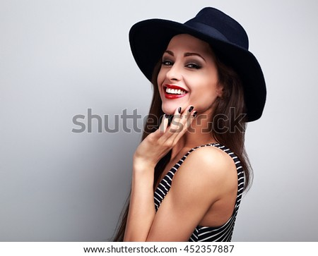 Stock Photo Happy smiling female model in black elegant hat on blue background