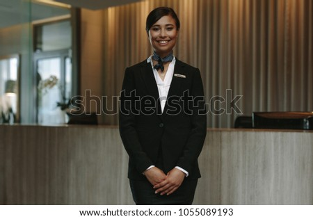 Happy smiling female receptionist in hotel. Beautiful concierge in uniform waiting for welcoming the guests. #1055089193