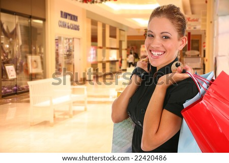 happy smiling female shopper holding shopping bags at shopping center