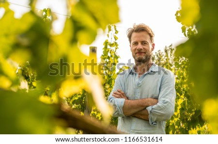 Happy smiling forty years old caucasian farmer standing proud in front of a vineyard. Agriculture or gardening - country outdoor scenery, warm sunset light.
