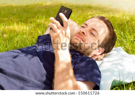 Happy Smiling Forty Years Old Caucasian Man Looking At Mobile Phone While Laying On Grass In Park During A Sunny Summer Day