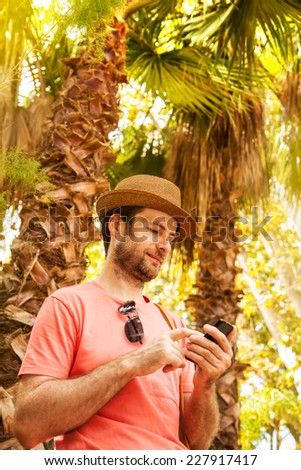 Happy smiling forty years old caucasian tourist man looking at mobile phone outdoor among exotic palm trees - summer holiday traveling