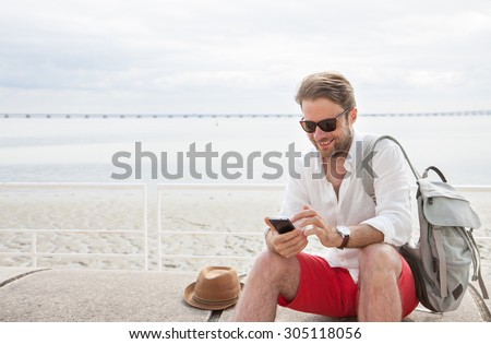 Happy smiling forty years old caucasian tourist man looking at mobile phone outdoor. Beach and sea as background - summer holiday traveling.