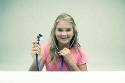 Happy smiling friendly little blond girl holding a stethoscope in her hand in a healthcare or medical concept over a white background