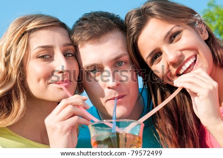 Happy smiling friends drinking with plastic straw a cold drink in summer