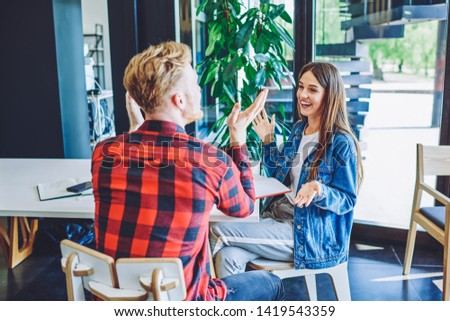 Happy smiling friends enjoying live communication in cafe interior during leisure time, cheerful successful male and female in trendy outfit discussing ideas for project and talking on publicity area