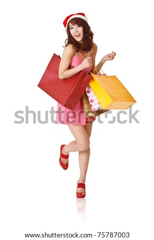 Happy smiling girl holding shopping bags and wearing Christmas hat, full length portrait isolated on white background.