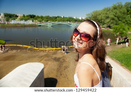 Happy smiling girl in sunglasses outside in the Tsaritsyno park, Moscow, Russia.