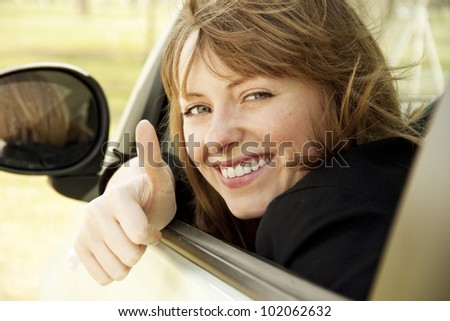 Happy smiling girl in the car looking throw window and showing thumb up