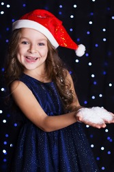 Happy smiling girl is wearing santa hat with white fake snow in hands in a studio background scene with lights for a holiday concept.