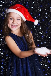 Happy smiling girl is wearing santa hat with white fake snow in hands in a studio background scene with lights and snow for a holiday concept.