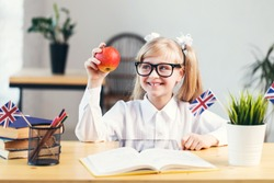 Happy smiling girl learning English language holding red apple in light stylish classroom, studying success concept