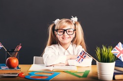 Happy smiling girl learning English language, working table with books, letters and flag