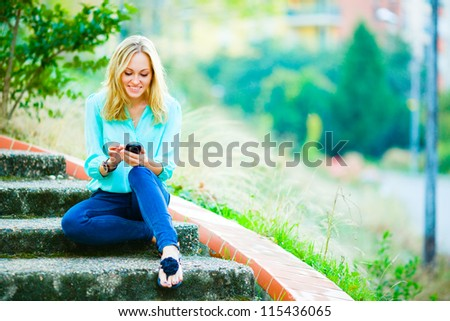 Happy smiling girl sitting on stairs writing a message on her mobile phone on city park background