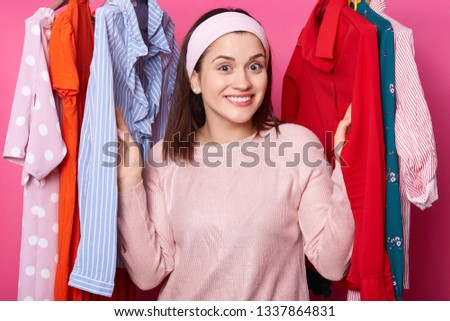 Happy smiling girl stands between hangers with blouses in fashion store. Cheerful woman visits boutique. Cute lady likes to go to mall. Beautiful young female on sale. Shopping and fasion concept.