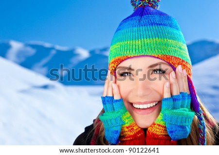 Happy smiling girl wearing colorful hat, beautiful female close up portrait, young pretty woman face over snow mountains blue background, winter fun outdoor, happy people concept