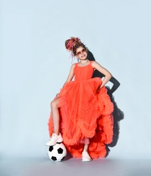 Happy smiling girl with colorful dreadlocks in sneakers stands with soccer ball under foot holding lifting fur hem of her bright coral dress. Girls in football concept