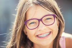 Happy smiling girl with dental braces and glasses.