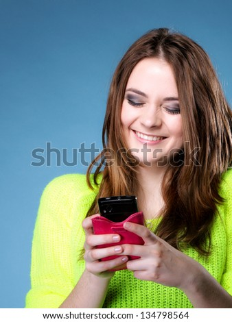 Happy smiling girl with mobile phone reads message , blue background