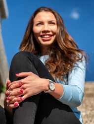 Happy smiling girl with wristwatch sitting outside with clasped hand. Focus on hands
