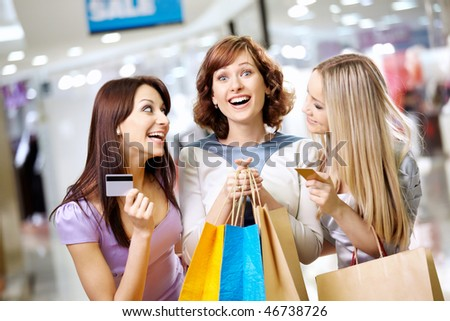 Happy smiling girls with credit cards in shop