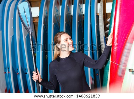 Happy smiling glad friendly  girl in wetsuit holding paddle, standing near rack with boards for paddleboarding #1408621859
