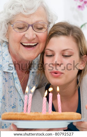 Happy smiling grandmother celebrating and giving a birthday cake to her grandson at home