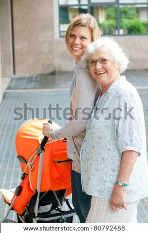 Happy smiling grandmother walking with her grandson and pushing a baby stroller, three generation family outdoor