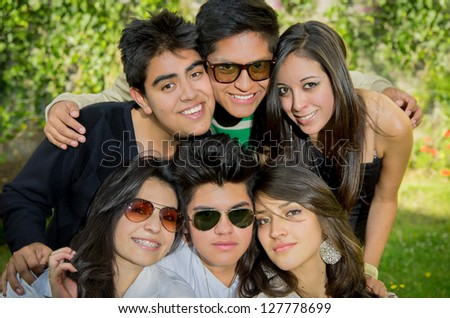 Happy smiling group of young friends posing together outdoor in the park