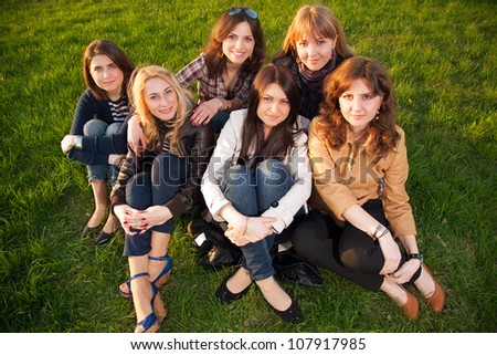 Happy smiling group of young friends sitting  together on the green grass outdoor in the park