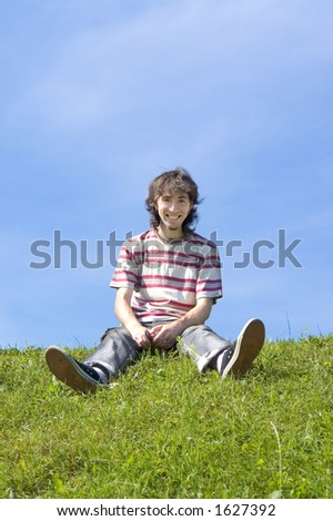 Happy Smiling Guy Sitting On The Grass