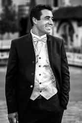 Happy smiling handsome groom in elegant suit closeup b&W